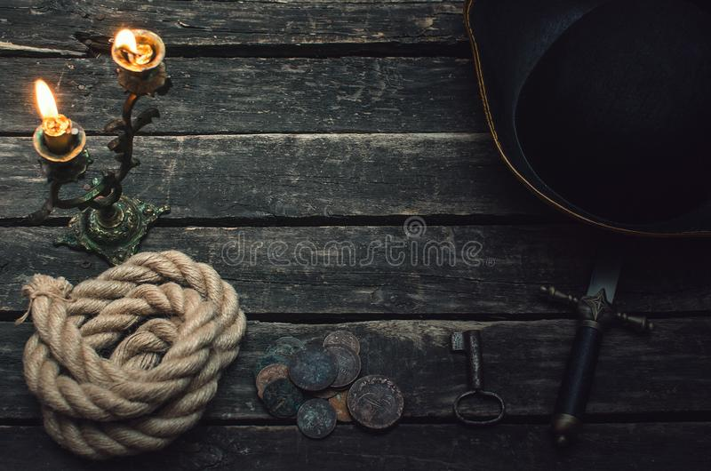 Pirate table. Pirate captain table with pirate hat, mooring rope, weapon, coins and burning candle. Treasure hunter concept stock images