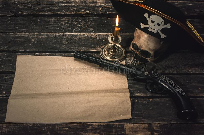 Pirate table. Pirate treasure map with copy space, pirate captain hat, human skull, musket and burning candle. Treasure hunter concept background stock photography