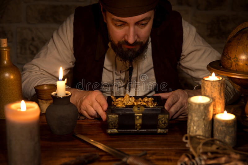Pirate with a treasure of gold, a lot of candles and old accessoires. A pirate with a treasure of gold, a lot of candles and old accessoires royalty free stock image