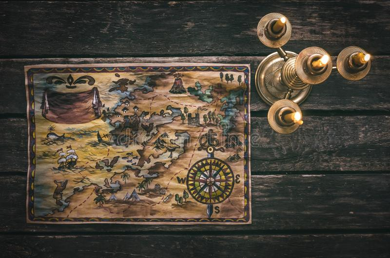 Treasure map. Pirate treasure map and burning candle on aged wooden table background. Treasure hunt concept. Sea travel stock photo