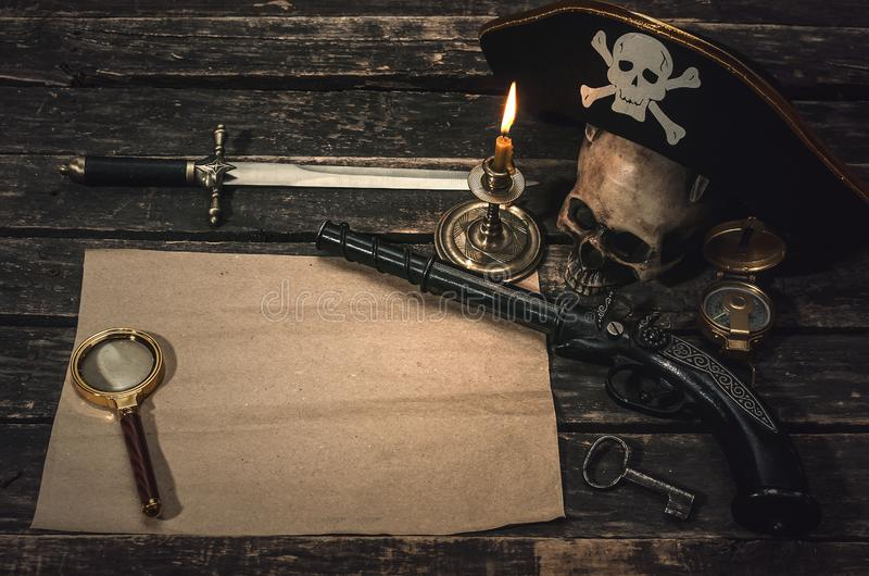 Pirate table. Pirate treasure map with copy space, pirate captain hat, compass, magnifying glass, human skull, musket, dagger and burning candle. Treasure stock photos