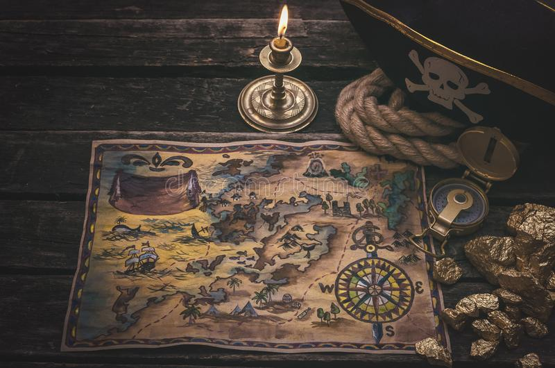 Treasure map. Pirate treasure map, gold nuggets and pirate hat on aged wooden table background. Sea travel stock photo