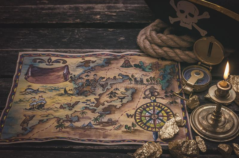 Treasure map. Pirate treasure map, gold nuggets and pirate hat on aged wooden table background. Sea travel stock image