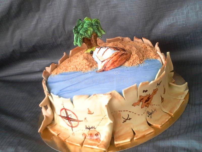 Piratee la pasta de azúcar de la torta con la nave, la palma, la arena y el mapa de las riquezas del oro fotos de archivo
