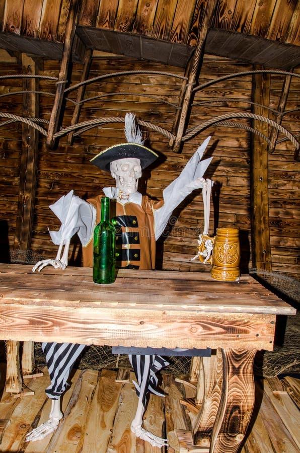 Pirateie o assento de esqueleto na tabela com caneca de cerveja fotografia de stock