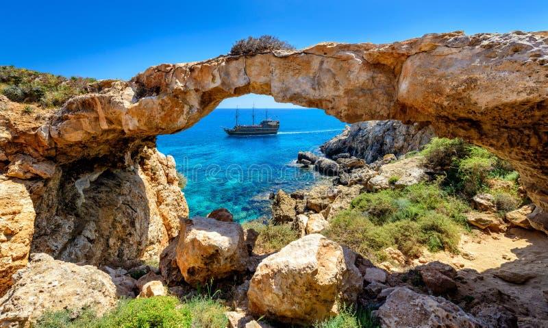 Piratenschiff durch Felsenbogen, Zypern stockbild