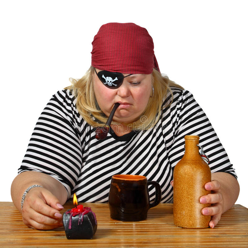 Pirates dream. Chubby woman in pirate costume sits near table with candle, mug, bottle and tobacco pipe. Genre portrait isolated on white background royalty free stock images