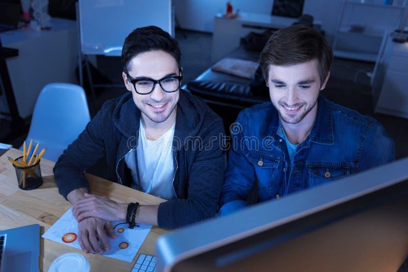 Pirati informatici allegri del genio che incidono in un sito Web di governo fotografie stock libere da diritti