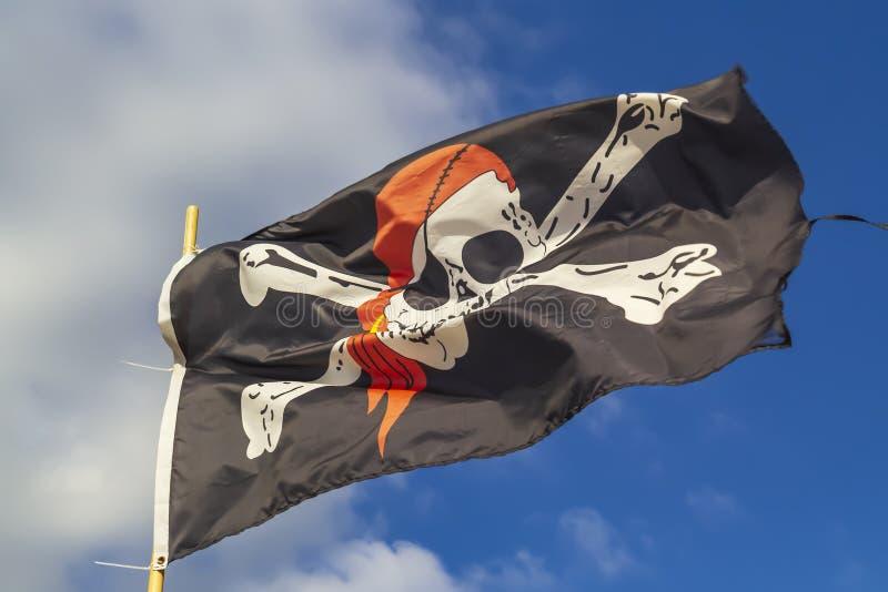Piratkopiera flaggan 'Jolly Roger 'på en bakgrund av blå himmel med moln på en ljus sömnig dag royaltyfri fotografi
