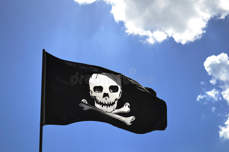 Piratkopiera flaggan mot blå himmel arkivbild