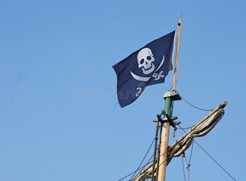 Piratkopiera flaggan som flyger ovanför sjörövareskeppet royaltyfri fotografi