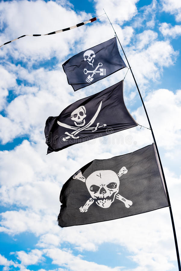 Piratkopiera flaggor i vinden arkivbild