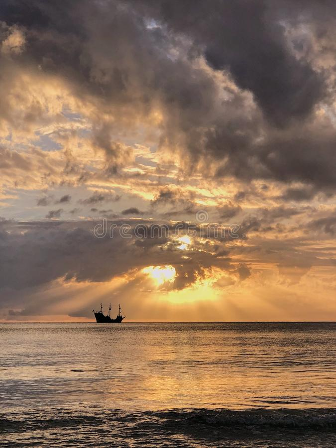 Piratkopiera skeppet på solnedgången med moln arkivfoton