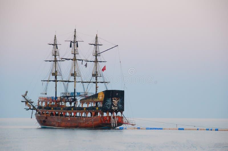 Piratkopiera skeppet som seglar typ som tidigt på morgonen förtöjas på pontonpir arkivfoto