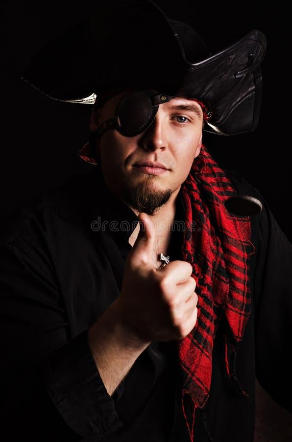 Piratkopiera vem kastar ett mynt in i luften arkivbild