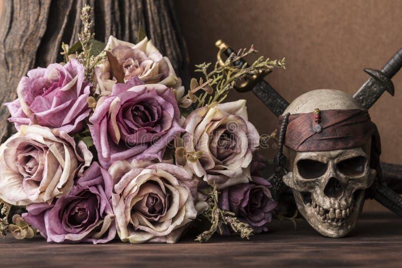 Piratkopierar purpurfärgade rosor för bukett med skallen och två svärd royaltyfri fotografi