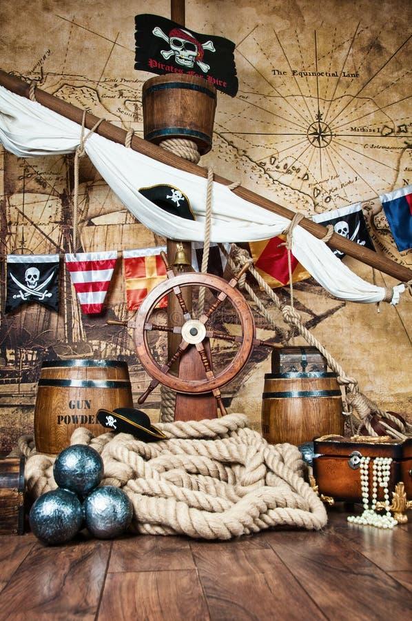 Piratkopierar skeppdäcket med den styrninghjulet och flaggan royaltyfri fotografi