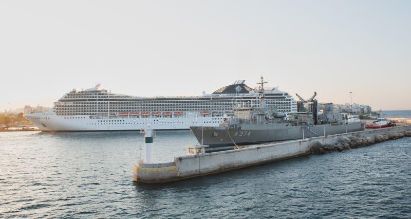 Pireaus Grecia 17 de julio de 2018: Barco de cruceros en el muelle con shi de la marina de guerra fotos de archivo libres de regalías