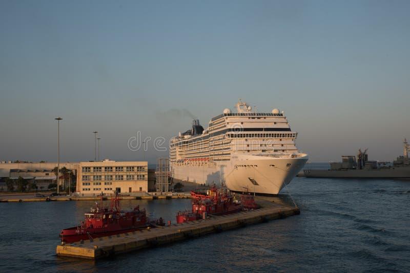 Pireaus Griekenland 17 Juli, 2018: Cruiseschip bij dok met fireboat stock foto's