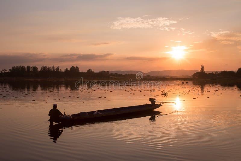 Pirogue de pêche traditionnelle au coucher du soleil sur Huai Luang Reservoir photographie stock libre de droits
