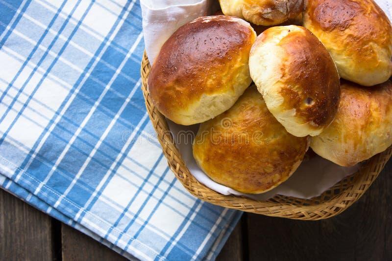 Pirozhki ruso, empanadas cocidas o empanadas en cesta con el jarro de leche Visión superior foto de archivo libre de regalías