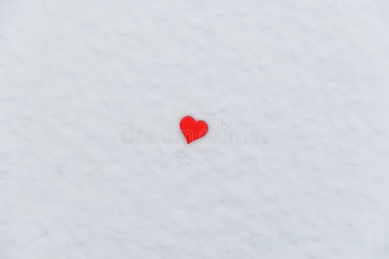 Piruleta en forma de coraz?n en la nieve D?a del `s de la tarjeta del d?a de San Valent?n Invierno, febrero, amor fotografía de archivo
