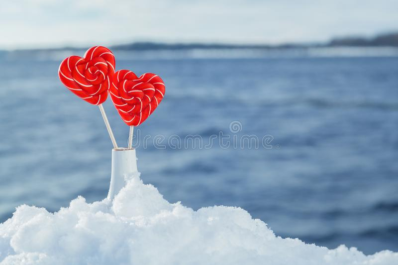 Piruletas de los corazones en la nieve en el fondo de las ondas del mar Fecha romántica, declaración del amor, el día de tarjeta  imagen de archivo