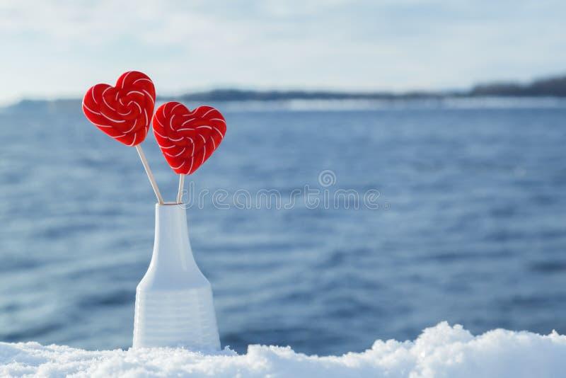 Piruletas de los corazones en la nieve en el fondo de las ondas del mar Fecha romántica, declaración del amor, el día de tarjeta  imagenes de archivo
