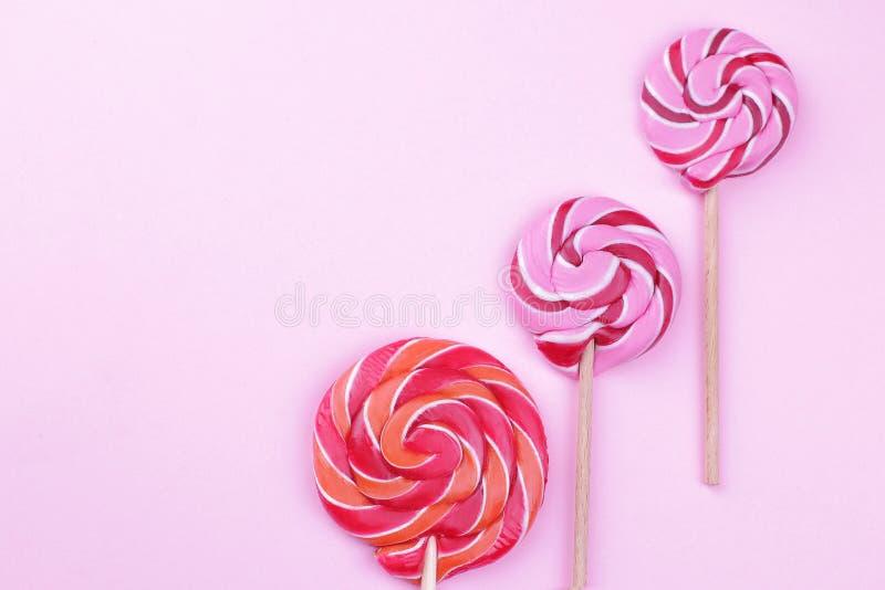 Piruletas multicoloras en un palillo en un fondo brillante rosado foto de archivo libre de regalías