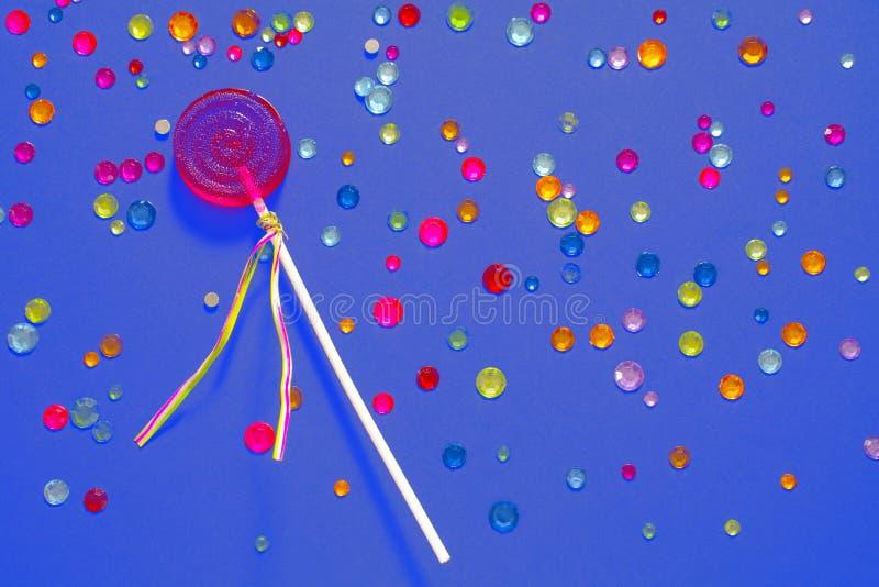 Pirulito redondo dos doces da cor vermelha em um fundo roxo com cristais de rocha multi-coloridos Conceito doce dos doces fotos de stock royalty free