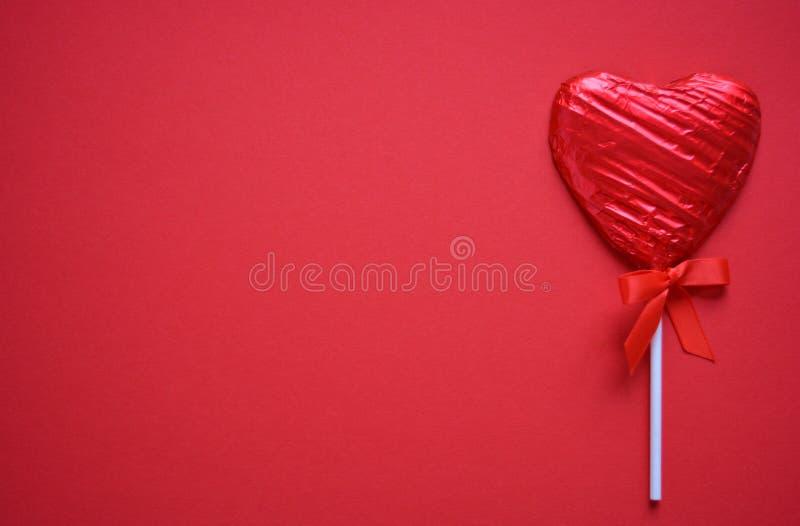 Pirulito vermelho isolado no fundo vermelho liso fotografia de stock royalty free