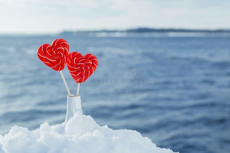 Pirulitos dos corações na neve no fundo de ondas do mar Data romântica, declaração do amor, o dia de Valentim fotografia de stock royalty free