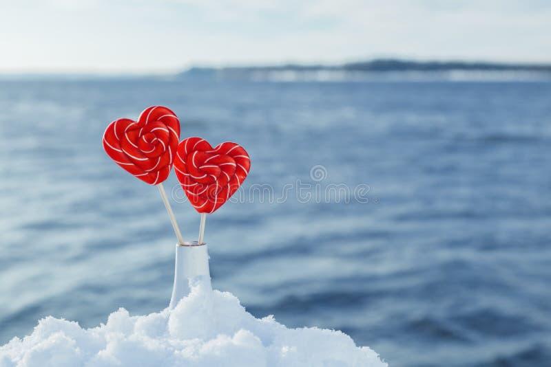 Pirulitos dos corações na neve no fundo de ondas do mar Data romântica, declaração do amor, o dia de Valentim imagens de stock royalty free