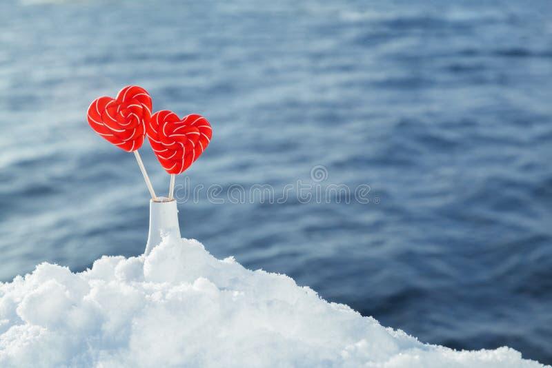Pirulitos dos corações na neve no fundo de ondas do mar Data romântica, declaração do amor, o dia de Valentim foto de stock