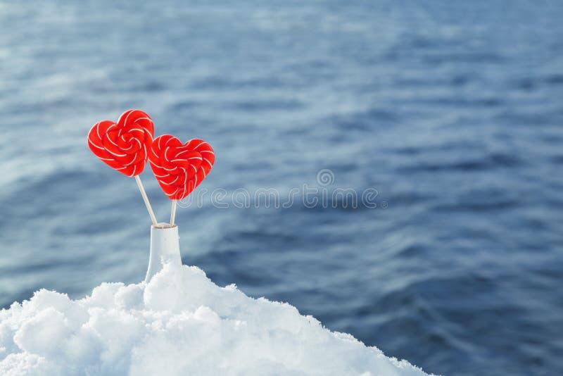 Pirulitos dos corações na neve no fundo de ondas do mar Data romântica, declaração do amor, o dia de Valentim fotos de stock