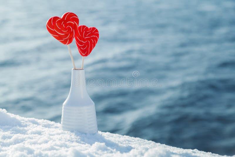 Pirulitos dos corações na neve no fundo de ondas do mar Data romântica, declaração do amor, o dia de Valentim fotos de stock royalty free