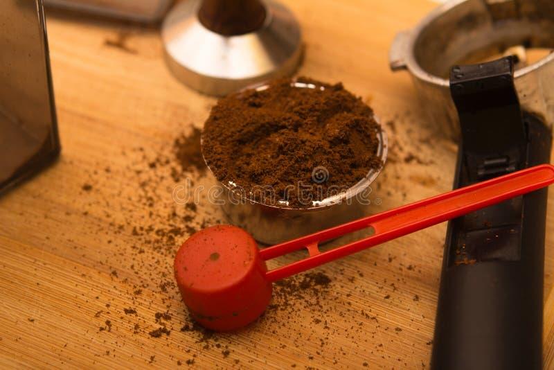 Pisón del café con café en cesta del filtro y el tenedor del filtro en un tablero de madera foto de archivo