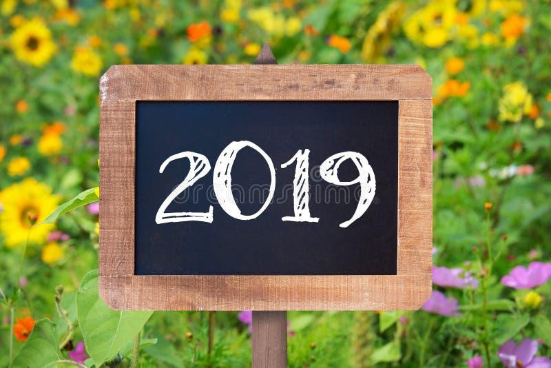 2019 pisać na drewnianym znaku, słonecznikach i dzikich kwiatach, zdjęcie stock