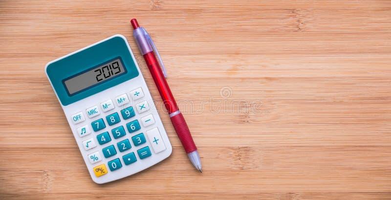 2019 pisać na kalkulatorze i piórze na drewnianym tle zdjęcia royalty free