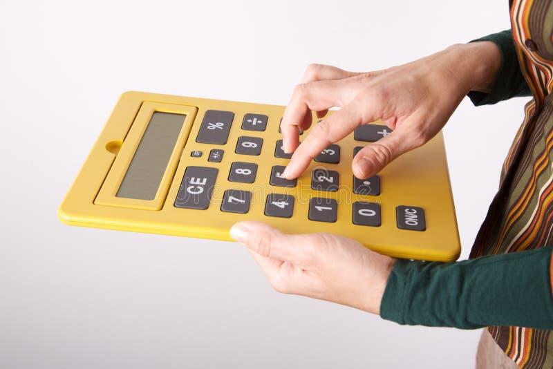 Pisać na maszynie na duży żółtym kalkulatorze obrazy royalty free