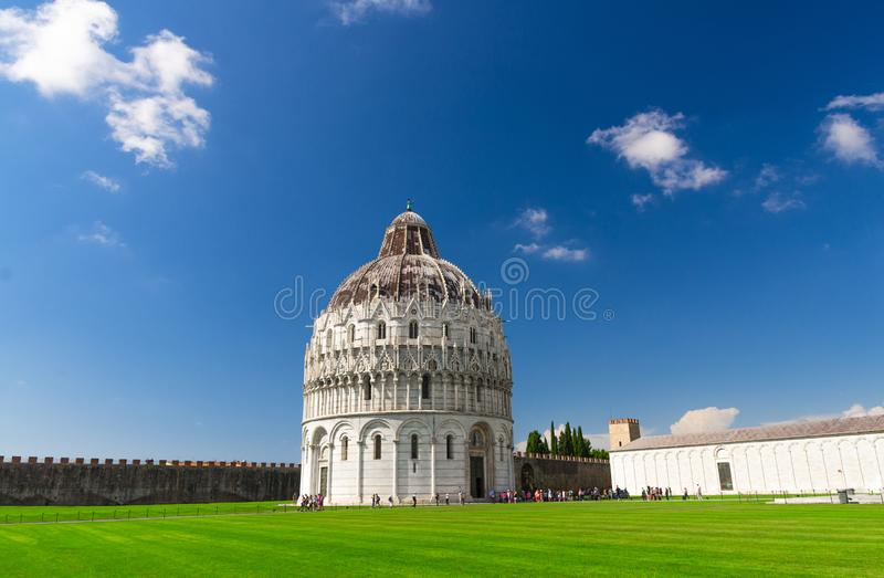 Pisa Baptistery Battistero di Pisa on Piazza del Miracoli Duomo square green grass lawn, city wall, Camposanto cemetery. Blue sky with white clouds copy space royalty free stock photo