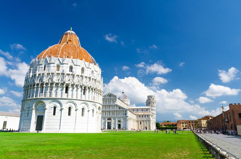 Pisa Baptistery Battistero, Pisa Cathedral Duomo Cattedrale and Leaning Tower Torre on Piazza del Miracoli square. Green grass lawn, blue sky with white clouds stock images