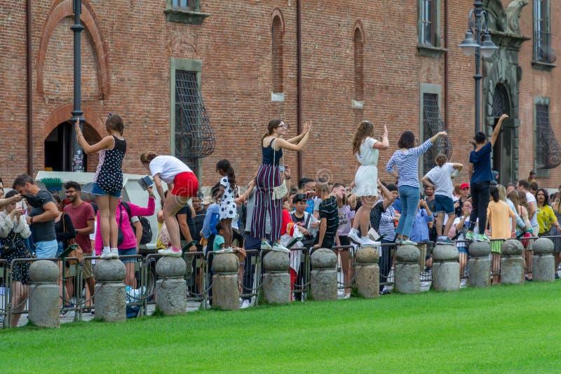 PISA ITALIEN - Juli 2019: Turister som framme poserar och tar bilder av det berömda lutande tornet av Pisa fotografering för bildbyråer