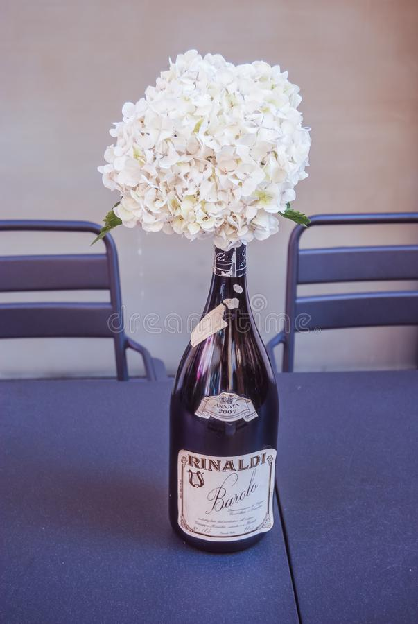 Bouquet of white flowers in a Rinaldi barolo 2007 red italian wine bottle royalty free stock photography