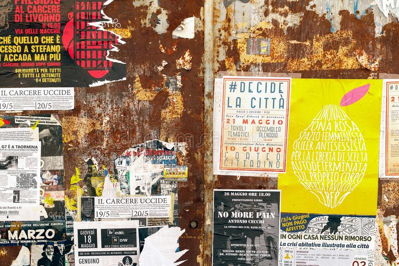 Rusty doors covered by torn promotional posters and stickers on royalty free stock photography