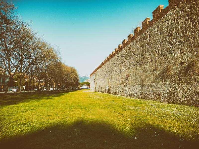 PISA, ITALY - MARCH 22, 2018: Ancient city walls surrounded by b royalty free stock images