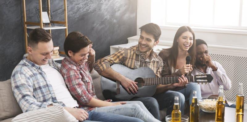 Pisak i kruk Przyjaciele bawić się gitarę i ma zabawę, śpiewacki karaoke zdjęcie stock