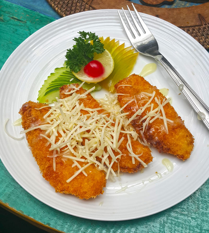 PISANG GORENG. Or more commonly known as banana fritters in golden crisp batter covered in condensed milk and sprinkled with cheese stock image
