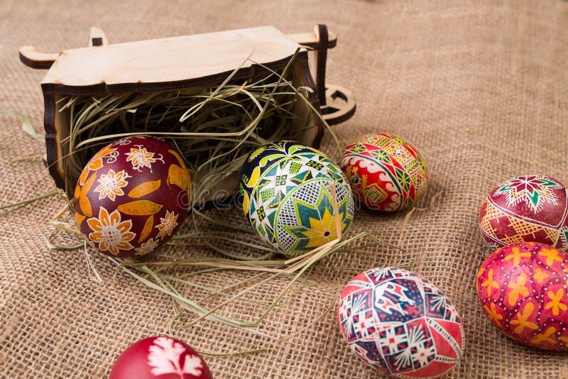 Pisanki con un carro y un heno antiguos de madera en harpillera Huevos de Pascua en estilo étnico Huevos de Pascua en lona foto de archivo libre de regalías