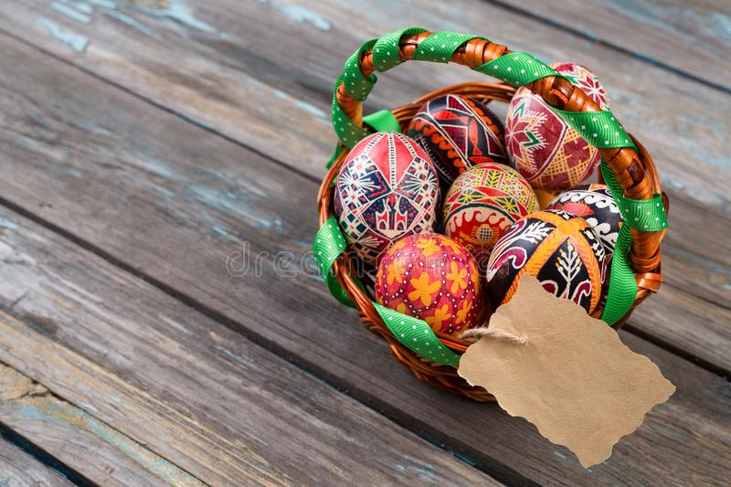 Pisanky in a wicker basket on a wooden background. Easter eggs on a wooden table. A busket with holiday eggs and blank. Paper gretting card. Painted eggs for stock images